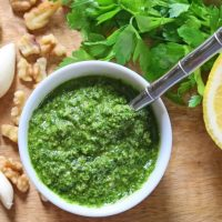 Lemon-Pepper Parsley Pesto is a simple way to use up extra parsley. It's like a sophisticated version of lemon-pepper seasoning and can be used in all the same ways you would traditional basil pesto. It's fresh, flavorful, and easy to make. Plus, it's a dairy free pesto that uses no cheese. Use it fresh or freeze it for later!